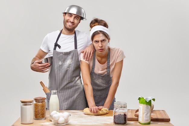 Attività domestiche. la casalinga e il marito stanchi preparano i biscotti fatti in casa, impastano la pasta per la cottura, seguono il passaggio della ricetta a casa, stanno insieme in cucina, isolati sul muro bianco. abilità culinarie