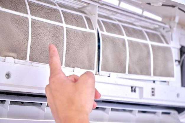 Концепция замены и очистки домашнего кондиционера. профессиональный ремонтник показывает грязные фильтры крупным планом