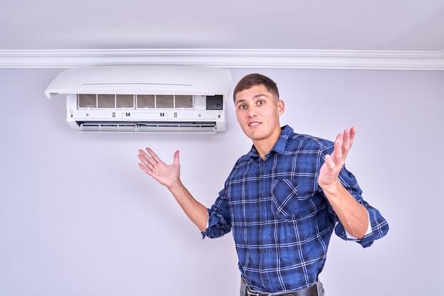 家庭用エアコンの交換とクリーニングのコンセプト。ショックを受けた顔のプロのフィクサーは汚れたフィルターを示しています