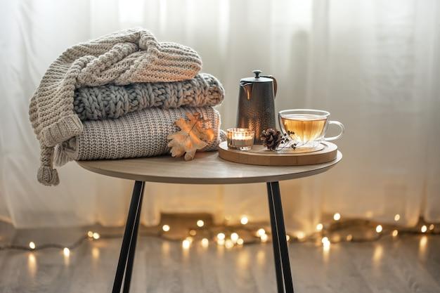 部屋の内部に、花輪のあるぼやけた背景にお茶とニットのセーターを置いた、家の秋の構図。