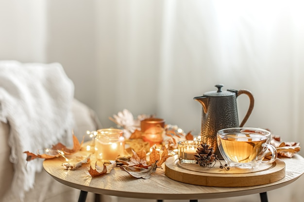 Home autumn composition with tea, dry leaves and burning candles on blurred background, copy space.