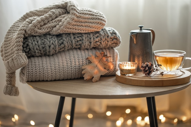 Home autumn composition with tea and knitted sweaters in the interior of the room, on a blurred background with a garland.