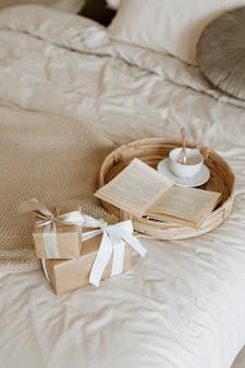 クラフト紙で包まれ、美しいリボンで飾られたギフトとギフトボックスのある家の背景。