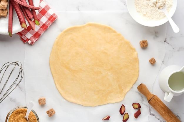 Концепция домашней выпечки из сырого теста, раскатанного с добавлением муки, воды, масла, сахара, ревеня