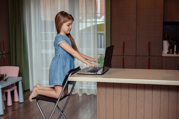 Home-based distance education of children during quarantine. happy child girl with long hair in jeans dress doing homework using laptop sitting at home in the kitchen