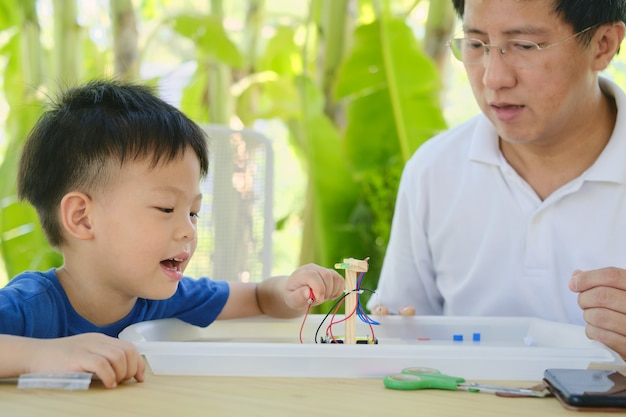 Home – based learning (hbl), parent sitting homeschooling with little kid, asian father and son having fun making easy diy stem traffic light toy kit at home, educational toys for young children