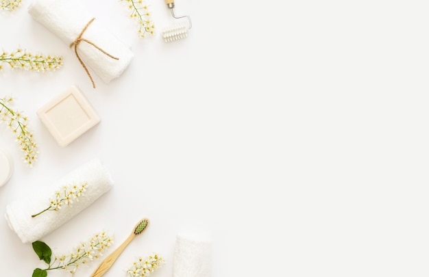 Home beauty essentials & home self care concept. flowering branches of bird cherry on white baground. white candle, soap, cream, towels. copy space. flat lay.