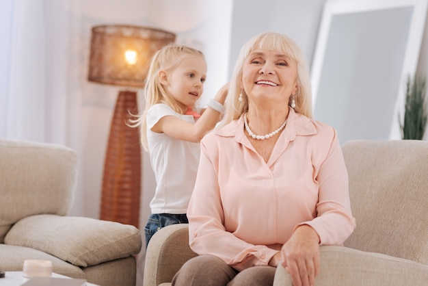 Home beauty salon. cheerful positive aged woman sitting on the sofa and smiling while having her hairstyle made