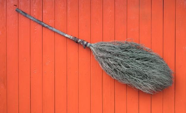 Домашняя метла на оранжевом фоне