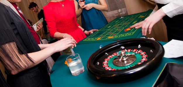 ホームカジノ。男性と女性がルーレットをします。数字にお金とチップを使って賭けをします。ゲームテーブルの緑の布。大人向けのギャンブルゲーム。すべての賭けが受け入れられ、これ以上の賭けはありません