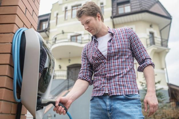Домашняя зарядная станция. серьезный молодой взрослый человек в повседневной одежде, стоящий возле зарядной станции на открытом воздухе в зоне домовладения
