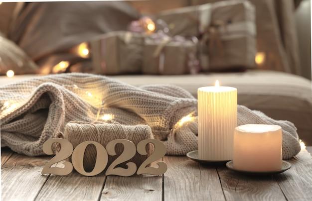 흐릿한 실내 배경에 장식용 목재 2022 숫자, 양초, 장식 세부 사항이 있는 홈 크리스마스 구성.