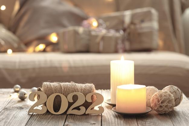 Composizione natalizia domestica con numeri decorativi in legno 2022, candele e dettagli decorativi su uno sfondo interno sfocato della stanza.