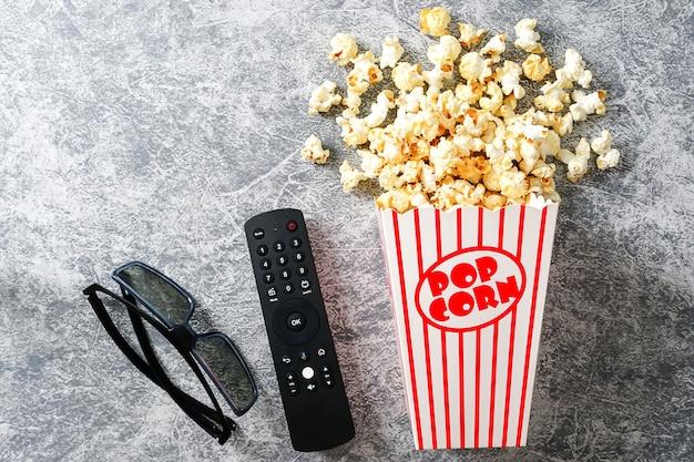 로프트 배경의 종이컵 3d 안경 및 tv 리모컨에 있는 홈 시네마 카라멜 팝콘