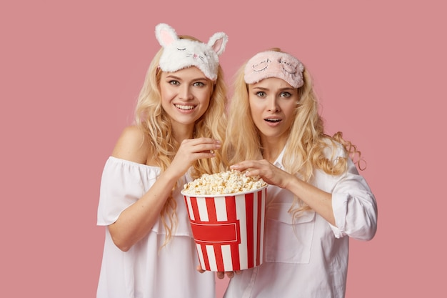 Home cinema online. young women in pajamas and sleep masks watching a movie at home on isolation in front of a television with popcorn