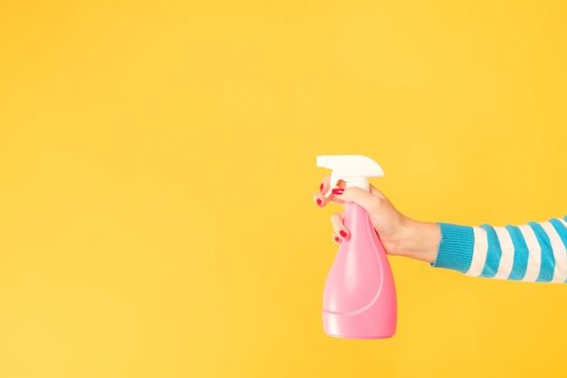 家の掃除の雑用。アトマイザーで武装した女性の手。黄色の背景にスペースをコピーします。