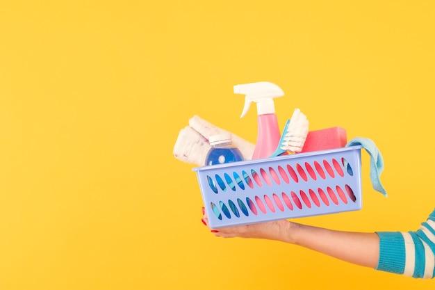 家庭用クリーニング製品。ハウスキーピングのコンセプト。物資の入ったバスケットを持っている手。黄色の背景にスペースをコピーします。