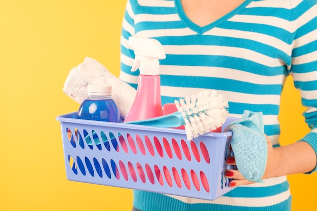 家庭用クリーニング製品。ハウスキーピングのコンセプト。基本的な物資がセットされたバスケットを保持している女性。