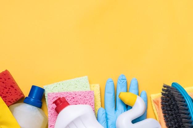 Домашние чистящие средства на желтом. ассорти из разнообразных материалов внизу