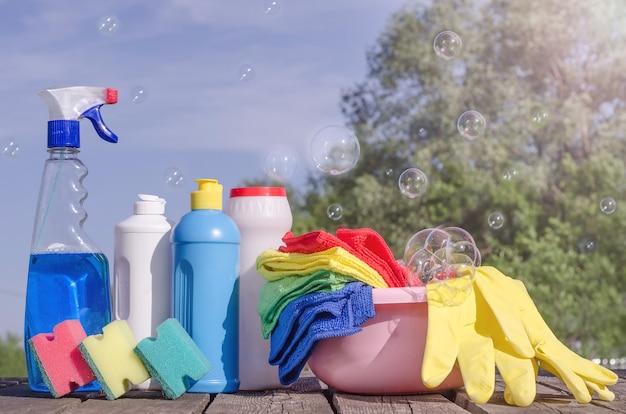 Домашние чистящие средства с красочными салфетками, губками на голубом небе с мыльными пузырями. генеральная уборка, профилактика вирусных заболеваний. уборка в доме, в квартире.