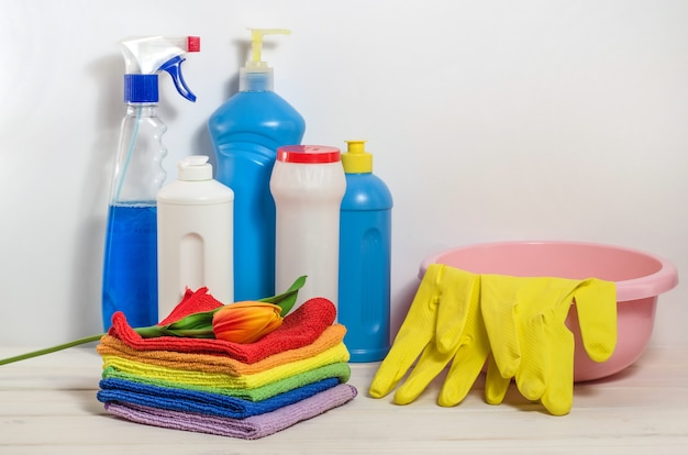 Home cleaning products with colorful napkins on a white space