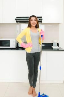부엌에서 걸레 청소 바닥을 가진 가정 청소 서비스 여성