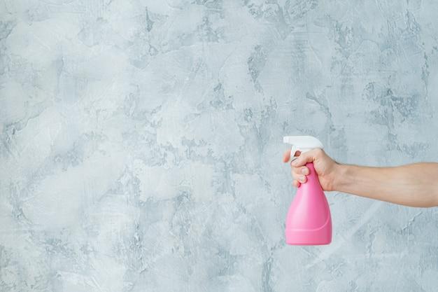 家の掃除戦略。窓拭き。アトマイザーを持っている手。コピースペース