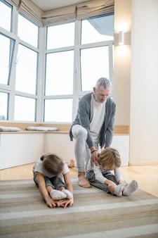 Домашний тренер. отец тренирует своих детей дома, заставляя их правильно растягиваться