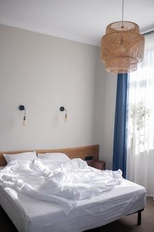 Домашний уют. мягкая удобная уютная кровать у белой стены с лампами в изголовье спальни, освещенными дневным светом