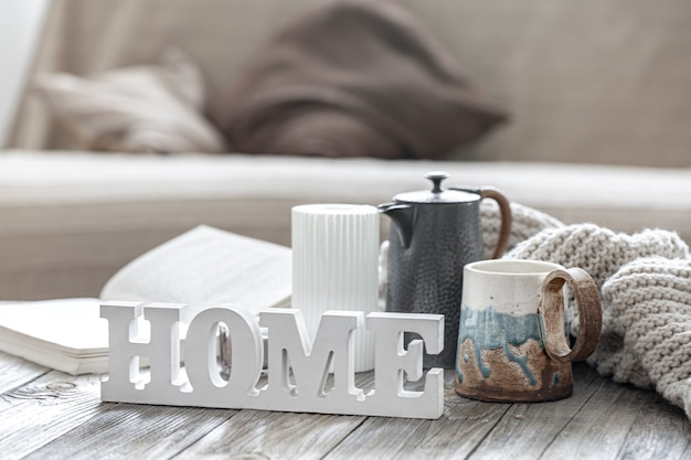 Home composition with the decorative word home, tea, knitted element and decor details on a blurred background of the interior of the room.