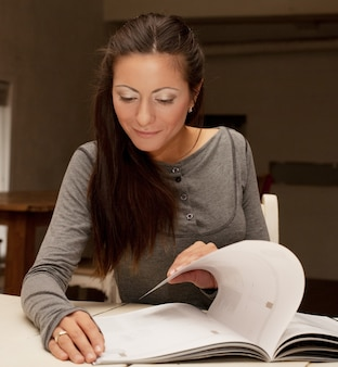 Home  concept - smiling young  woman reading magazine at home