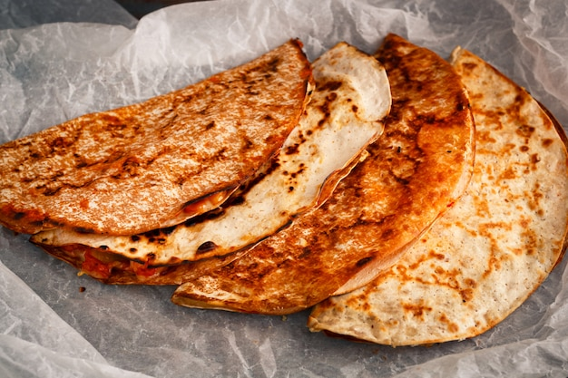 Home cooked mexican quesadilla is stacked on a parchment.