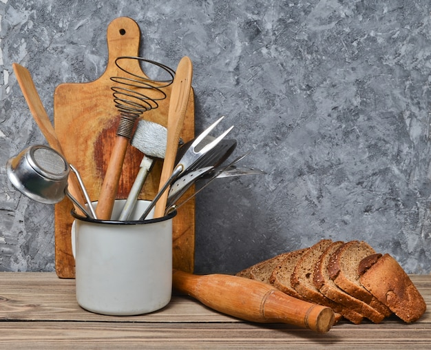 Home cooking, bakery. wooden board, kitchen tool, rye bread on a table on the background of a gray concrete wall.