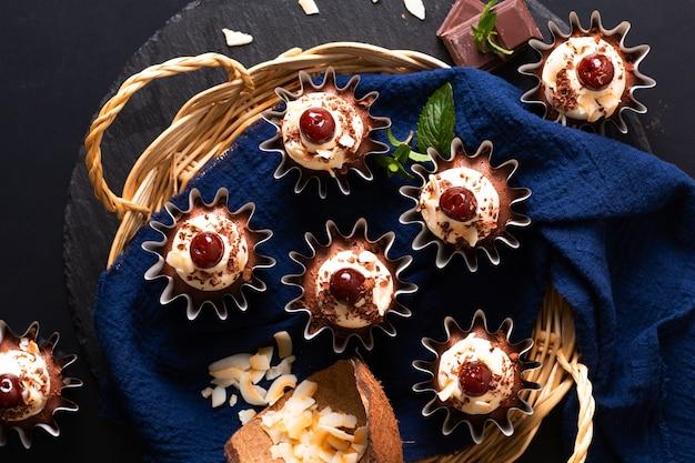 家庭料理のコンセプトコピースペースを持つ青いナプキンに自家製の黒い森のココナッツクリームカップケーキ