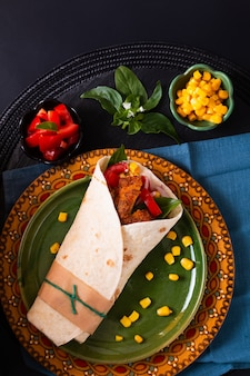 家庭料理のコンセプトオーガニック自家製フライドチキンのブリトートルティーヤサンドイッチカラープレートと黒のコピースペース