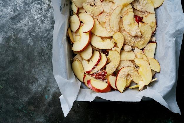 家庭料理のコンセプト。アップルパイの準備プロセス。りんごは生地の入ったベーキングトレイの上にすでにあります。上面図フラットレイ。