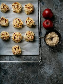 家庭料理のコンセプト。焼く準備ができているベーキングペーパーシートの上に置かれたリンゴの渦巻きの準備プロセス。リンゴと砂糖で飾られています。上面図フラットレイ。