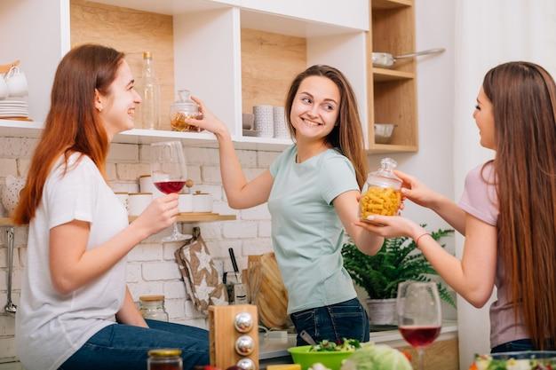 家庭料理のレジャー。夜のリラクゼーション。食事を準備している若い女性。話したり笑ったりします。