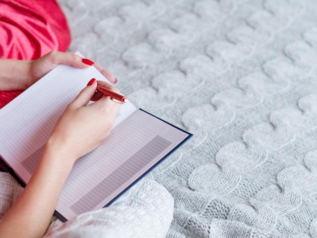 Домашняя еда. написание утреннего меню. женщина, сидящая в постели с пустой записной книжкой.