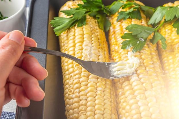 Рецепт домашнего приготовления кукуруза запеченная с солью, маслом и кинзой или петрушкой в фольге. концепция домашней еды. вегетарианское здоровое питание.