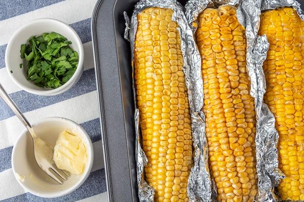 호일에 소금, 버터, 고수 또는 파슬리를 곁들인 구운 옥수수 요리법. 집에서 만든 음식 개념입니다. 채식 건강식.