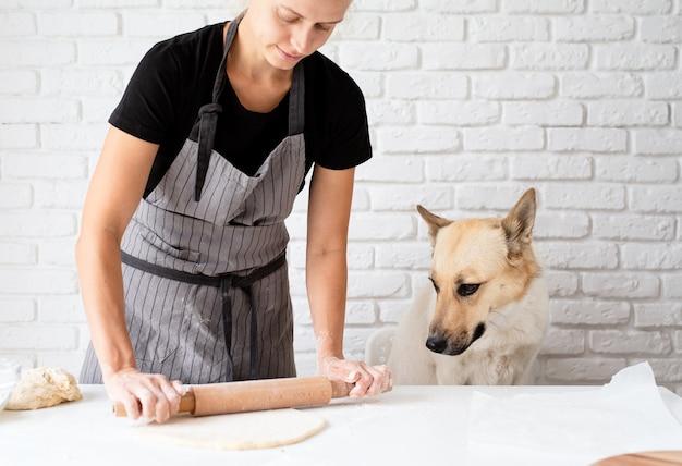 가정 요리. 그녀의 개가 옆에 앉아 집에서 반죽을 반죽하는 여자