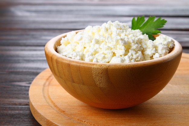 Home cottage cheese in a bowl on a wooden table.