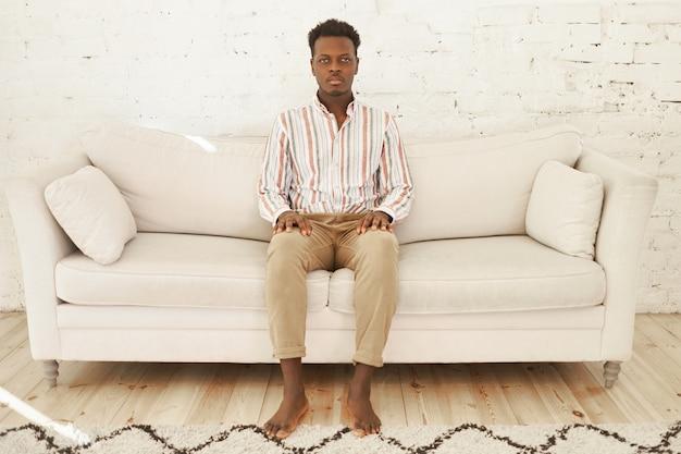 家、居心地のよさ、家庭性のコンセプト。リビングルームのソファに裸足で座っている深刻な若いアフリカ系アメリカ人男性