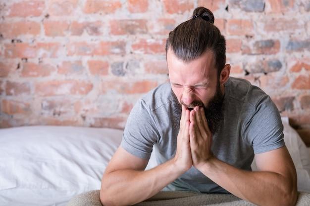 家の居心地のよさ。朝の怠惰。ベッドに座ってあくびをしている若い男。起きる時間。中二階のアパート。スペースをコピーします。