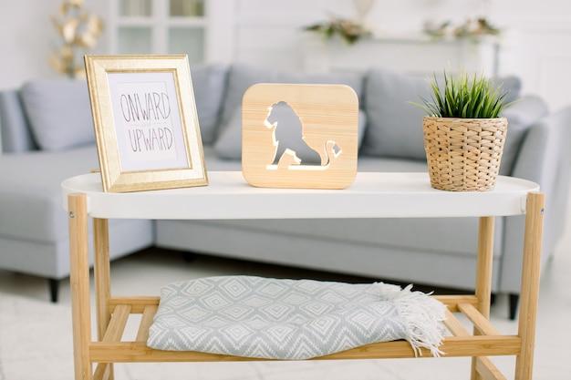 가정 아늑한 장식 및 액세서리. 사진 프레임, 사자 그림 장식 나무 램프, 고리 버들 화분에 인공 식물이있는 커피 테이블.