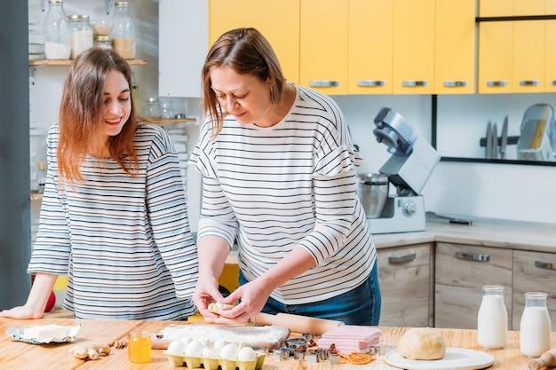 가정 요리 코스. 반죽으로 요리하는 방법을 가르치는 어머니는 진저 브레드 비스킷을 만듭니다.