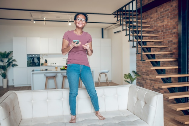 At home. a dark-skinned girl in eyeglasses and with a smartphone at home
