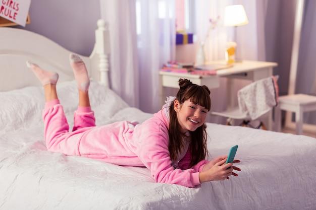 День дома. позитивно довольная девушка сохраняет улыбку на лице, используя свой новый смартфон