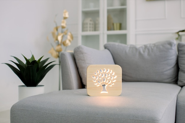 Home decor and accessories. wooden night lamp with tree picture, at stylish light home living room interior, on gray modern sofa.